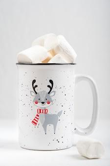 Tazza con stampa di cervi che indossano sciarpa piena di bevanda al cacao con marshmallow sul tavolo di legno bianco
