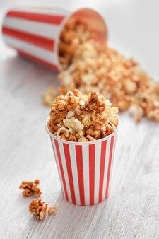 Tazza con gustosi popcorn al caramello sulla tavola di legno