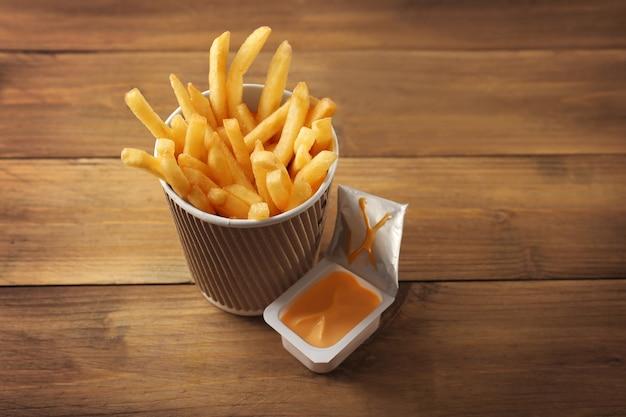 Tazza con gustose patatine fritte e salsa di formaggio su tavola di legno