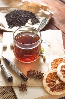 Tazza con tè, foglie di tè essiccate su carta kraft, zuccheri di zucchero, spezie, busta e maniglia su un tavolo di legno