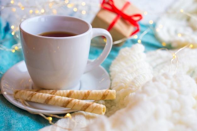 Tazza di tè su uno sfondo chiaro e un regalo per san valentino. romantica festa della mamma colazione.