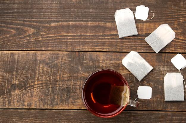 Tazza con tè e bustine di tè su un tavolo di legno marrone. vista dall'alto con spazio per il testo