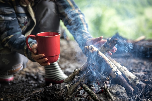 Una tazza con una bevanda calda durante le escursioni nei boschi accanto al fuoco.