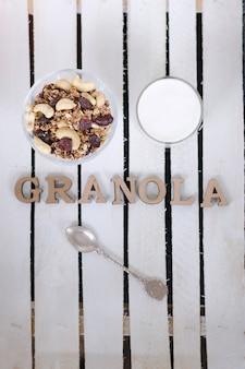 Tazza di yogurt, muesli, un cucchiaino e iscrizione di muesli. Foto Premium