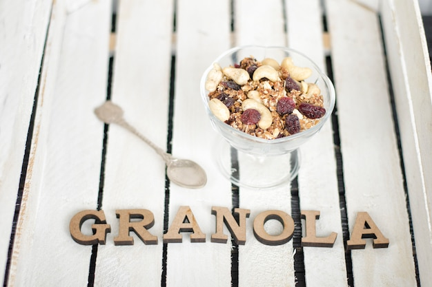 Tazza di yogurt, muesli, un cucchiaino e iscrizione di muesli.