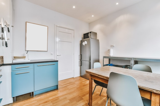 Armadi e fornello a gas con cappa di aspirazione situata vicino al tavolo con sedie contro le finestre in cucina leggera a casa