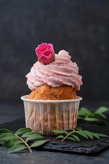 Cupcake decorato con rose. dessert su un piatto di ardesia nera. torte su uno sfondo scuro. Foto Premium