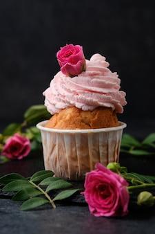 Cupcake decorato con rose. dessert su un piatto di ardesia nera. torte su uno sfondo scuro.