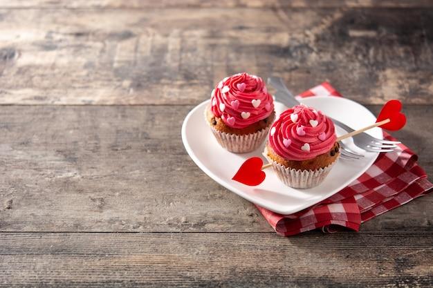 Cupcake decorato con cuori di zucchero e una freccia di cupido per san valentino sulla tavola di legno