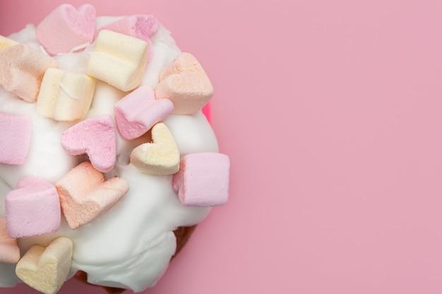 Cupcake con cuori di marshmallow su uno sfondo rosa closeup