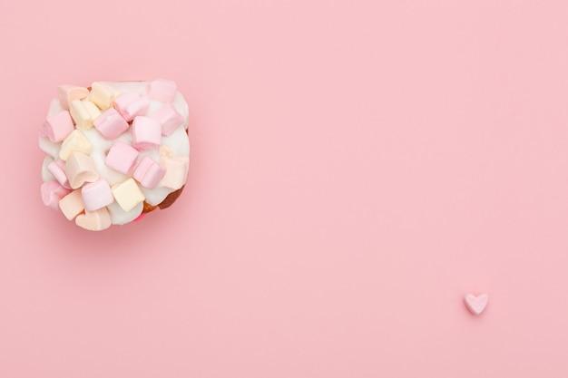 Cupcake con cuori di marshmallow su sfondo rosa con cuoricino in basso a destra