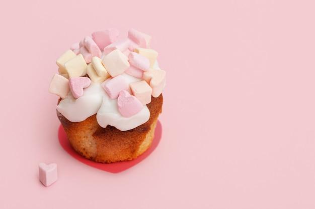 Cupcake con cuori di marshmallow su uno sfondo rosa con cuoricino vicino al muffin