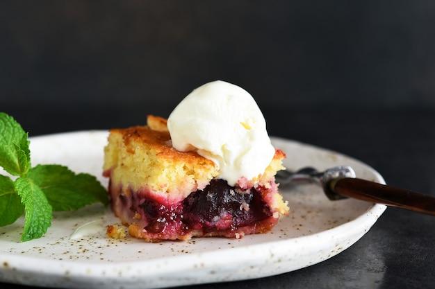 Cupcake con prugne e gelato alla vaniglia su sfondo scuro. torta di frutta con menta.