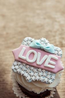 Il cupcake con la parola amore su uno sfondo marrone. san valentino