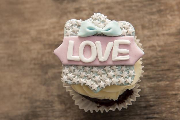 Il cupcake con la parola amore su uno sfondo marrone