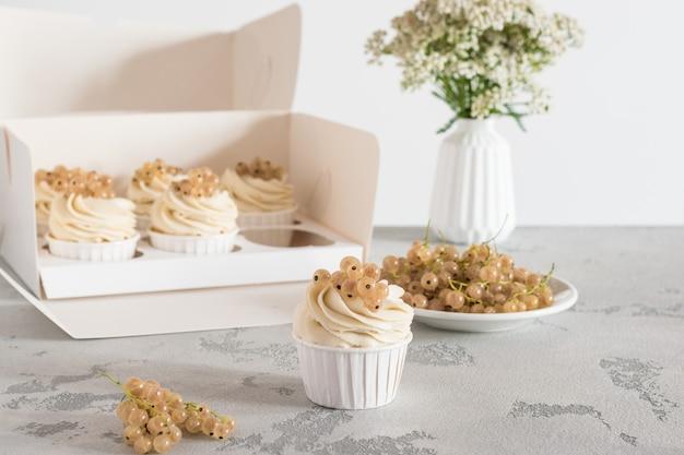 Tortine in una scatola con ribes bianco su una parete leggera, fiori in un vaso