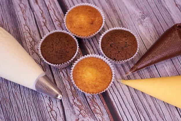 Cupcakes e sacchetti di pasticceria con crema di close-up.