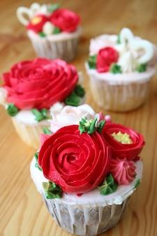 Tortine decorate con panna montata a forma di fiore rosso su un tavolo di legno con messa a fuoco selettiva