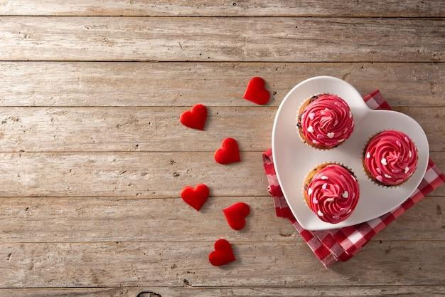 Cupcakes decorati con cuori di zucchero per san valentino sulla tavola di legno