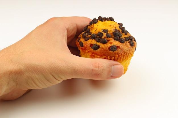 Cupcakes in mano su un primo piano bianco