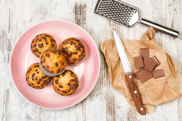 Tortine con gocce di cioccolato su un piatto rosa su un tavolo di legno