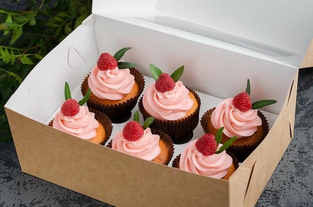 Cupcakes con crema di lamponi, decorati con lamponi in cima sulla carta da regalo.