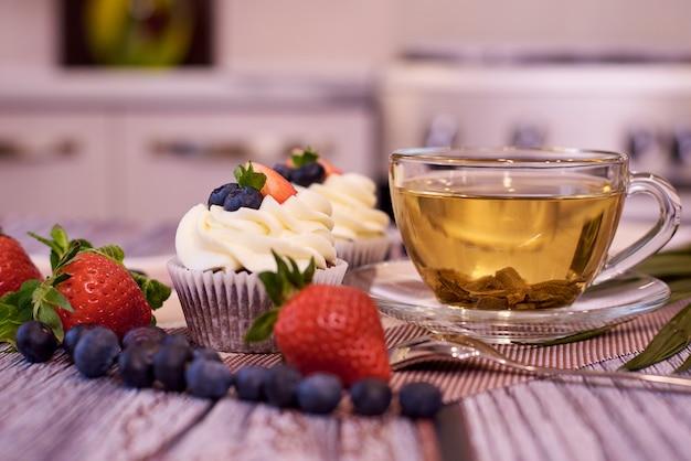 Cupcakes con fragole e mirtilli. cupcakes con una tazza di tè.
