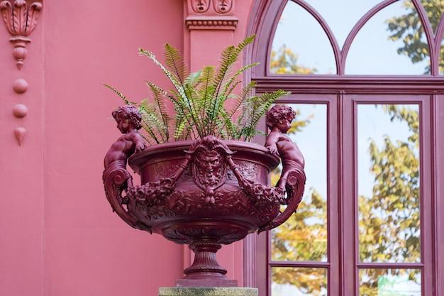 Scultura di aiuola di cupido. vaso di fiori romano, vaso con sculture nel giardino botanico di porto, portogallo