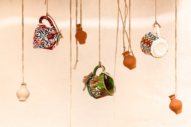 Tazze e vasi di terracotta appesi alle corde, il design e l'interno del ristorante per un bar, un modo creativo per posizionare gli oggetti in vendita
