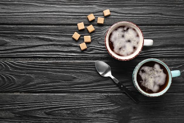 Tazze di caffè con zucchero su superficie in legno