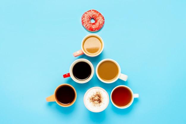 Tazze con bevande calde, caffè, cappuccino, caffè con latte, forma di albero di natale isolato