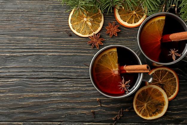 Tazze con vin brulè, ingredienti e rami di pino su legno