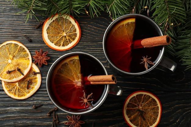 Coppe con vin brulè, ingredienti e rami di pino