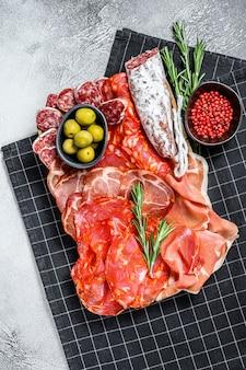 Piatto di carne stagionato di tapas spagnole tradizionali. chorizo, jamon serrano, lomo e fuet. sfondo grigio. vista dall'alto