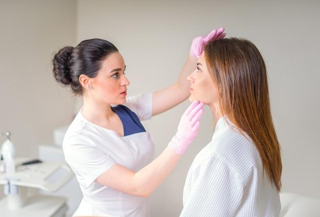 Curare i problemi della pelle. cosmetologo femminile guardando il viso del cliente attraverso la lampada di ingrandimento esaminando la sua pelle.