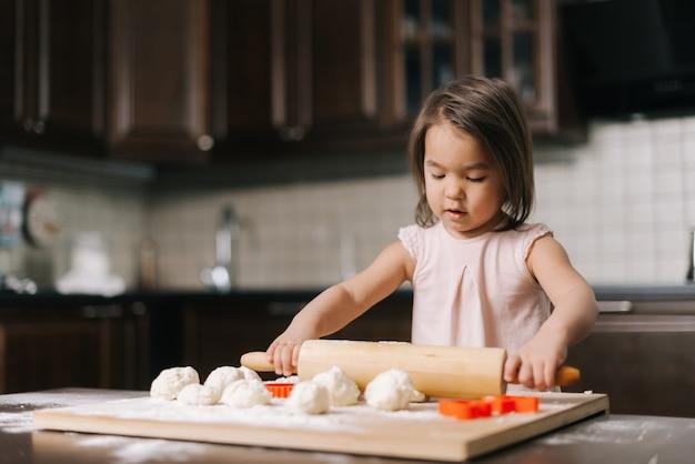 La bella bambina curiosa sta stendendo la pasta con il mattarello di legno al tavolo