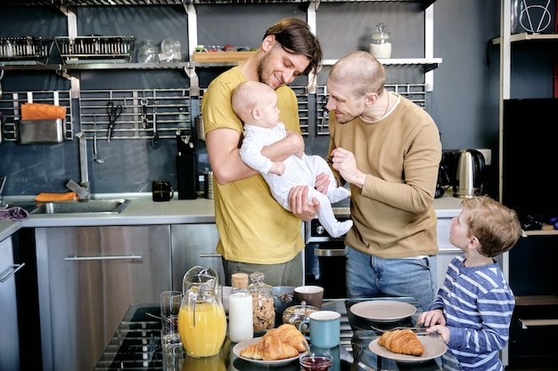 Ragazzo curioso che guarda i suoi allegri padri che giocano con il neonato in cucina