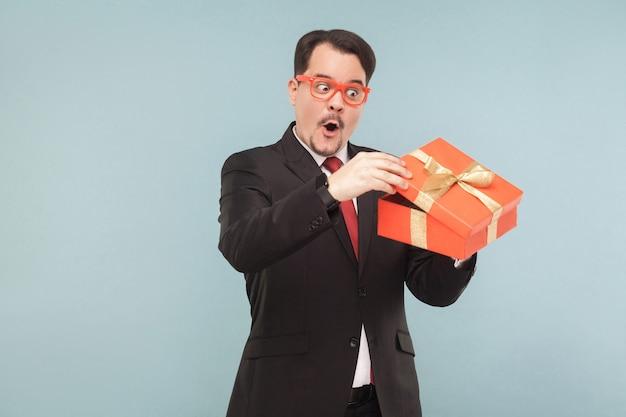 Uomo d'affari curioso che tiene in mano una scatola regalo rossa e guarda dentro