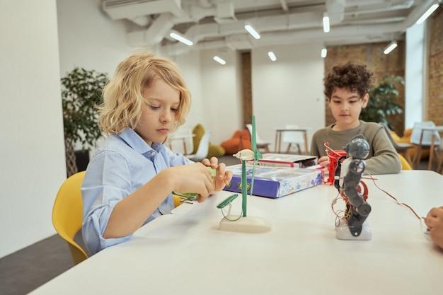 Curioso ragazzo caucasico che esamina un giocattolo tecnico pieno di dettagli mentre è seduto al tavolo insieme