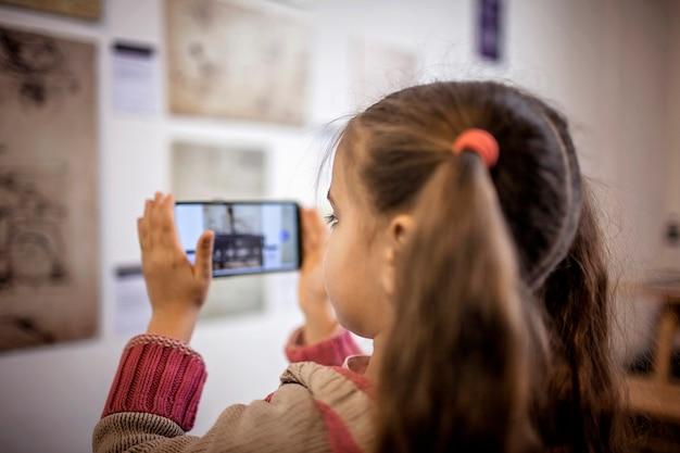 Ragazza curiosa che esplora una mostra d'arte contemporanea con l'applicazione mobile di realtà aumentata