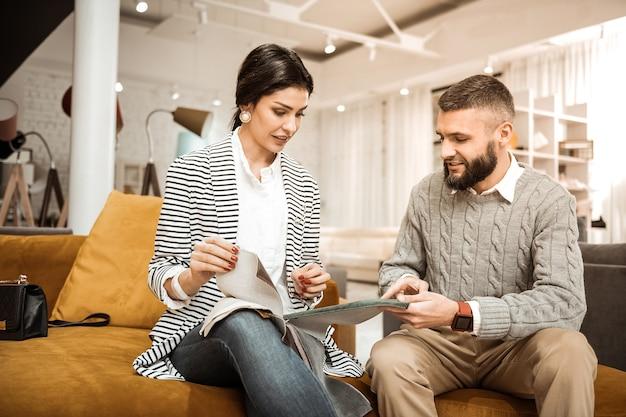 Curioso marito. coppia risoluta concentrata che ispeziona diversi pezzi di tessuto mentre sceglie la superficie per il futuro divano