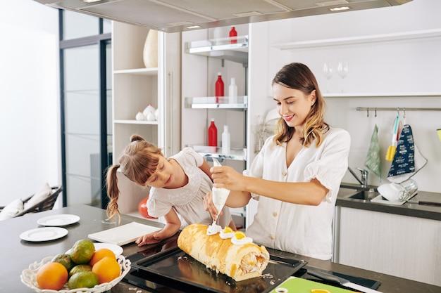 Bambina curiosa che guarda sua madre che decora il rotolo svizzero con fette d'arancia e panna montata