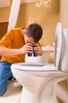 Uomo curioso con il binocolo guardando nella toilette. interno del bagno di lusso