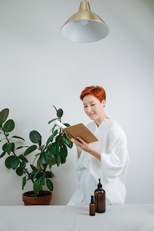 Donna curiosa dai capelli corti che guarda il taccuino ecologico con una copertina di cartone. fa finta di leggerlo.