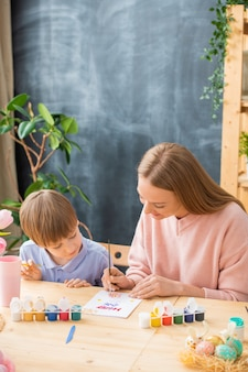 Curioso figlio seduto a tavola e guardando come madre che fa la carta di pasqua