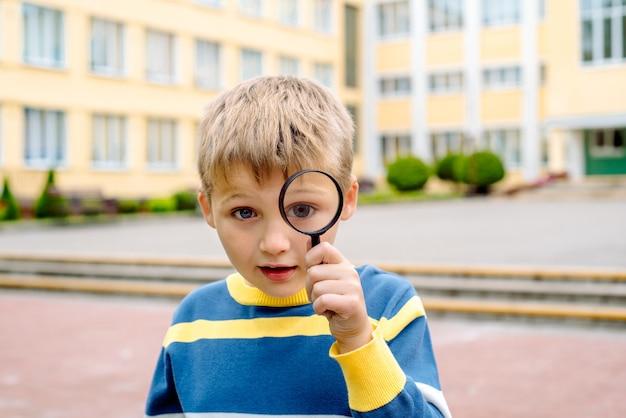 Ragazzo curioso sorpreso. uno scolaro con una lente d'ingrandimento vicino all'occhio nel cortile della scuola.