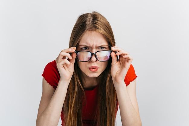 Donna curiosa con gli occhiali a fissare