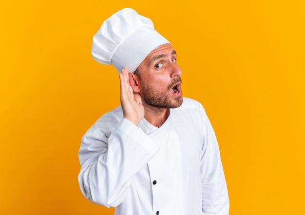 Curioso giovane maschio caucasico cuoco in uniforme da chef e berretto guardando la telecamera facendo non riesco a sentirti gesto isolato sul muro arancione