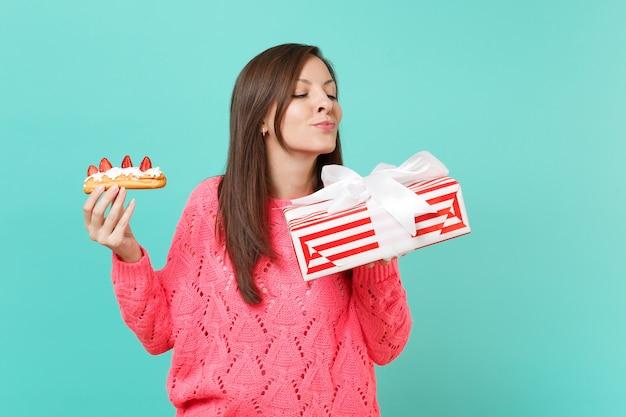 Ragazza curiosa in maglione rosa lavorato a maglia tenere torta eclair, scatola regalo a strisce rosse con nastro regalo isolato su sfondo blu. concetto di festa di compleanno di san valentino della donna. mock up copia spazio.