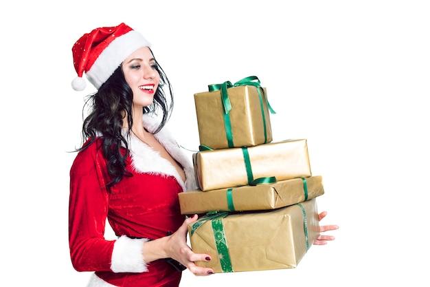 Curiosa giovane ragazza di santa, cappello di natale che tiene scatola con regalo presente isolato su sfondo bianco. concetto di festa di festa di celebrazione di felice anno nuovo. mock up copia spazio. babbo natale gioioso